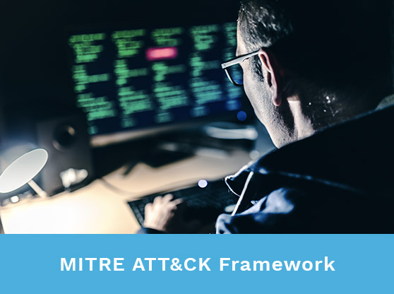 Looking over the shoulder of a man looking at monitors. Text reads: MITRE ATT&CK Framework