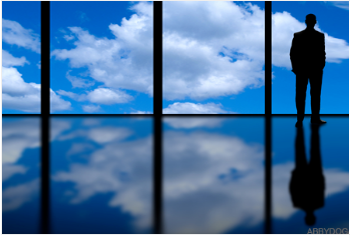 Man in suit staring out window at blue sky and clouds
